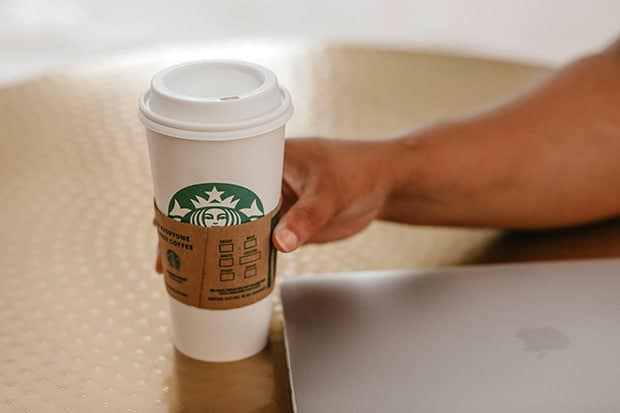 Hand places a Venti Starbucks cup next to a computer