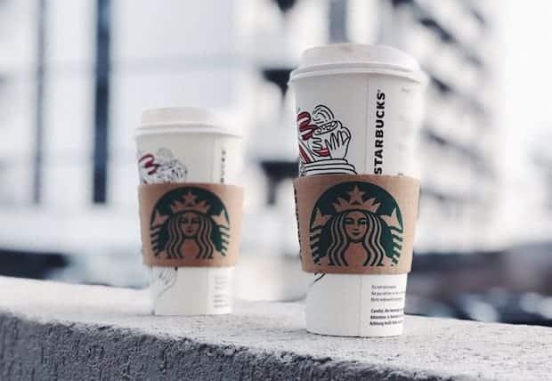 Venti and Grande Starbucks cups perched on a ledge