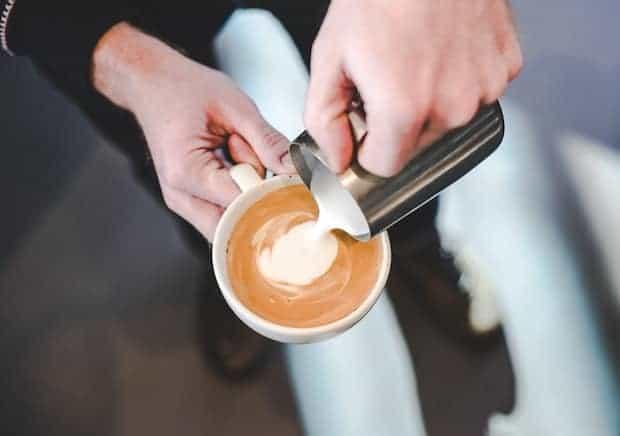 Barista pouring milk into a cappuccino