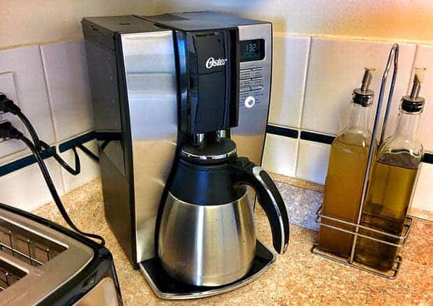 Stainless steel coffee pot on an Oster coffee maker
