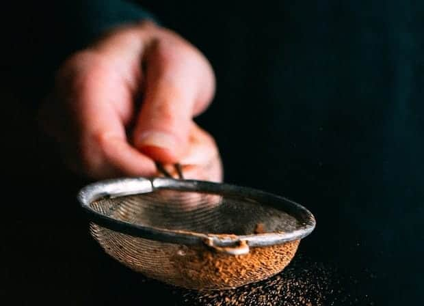 Hand holding a mesh sieve containing brown powder