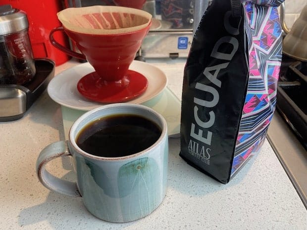 A cup of brewed coffee next to a bag of beans from Ecuador and a Hario V60 pour over cone in the background
