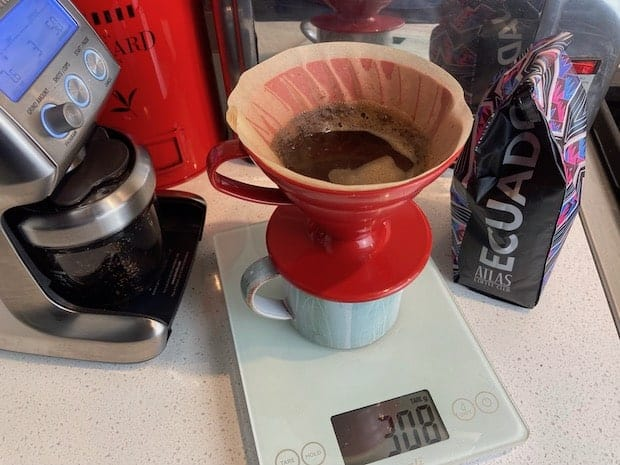 Pour over coffee brewing on a scale next to a bag of coffee from Ecuador