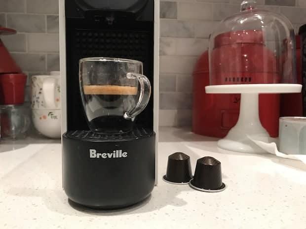 Breville Essenza Plus Nespresso machine on a kitchen counter with a brewed espresso on its platform
