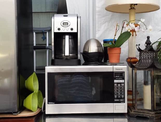 Cuisinart coffee maker sitting on top of a microwave oven on a kitchen counter
