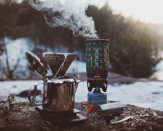Coffee brewing at winter campsite with a travel coffee grinder nearby