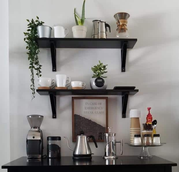 Coffee statin on a dark wood dressers with dark wood shelves on the wall above