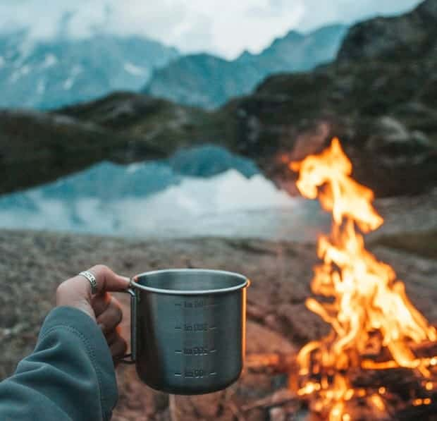 Hand holding up a tin coffee cup by a campfire