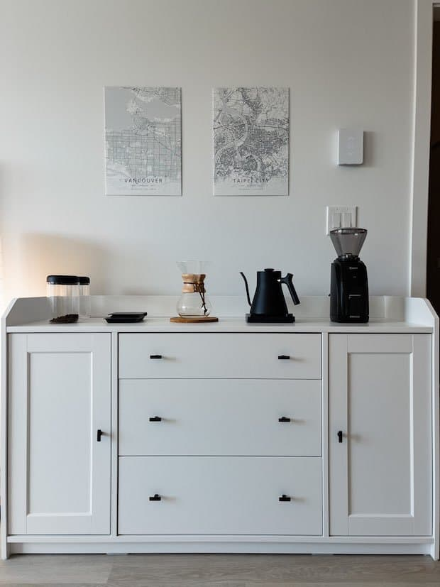Coffee station in white, set up on a dresser against the wall