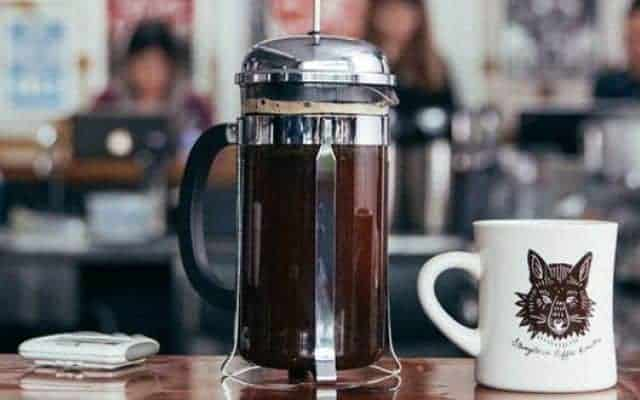 French press on a table next to a mug