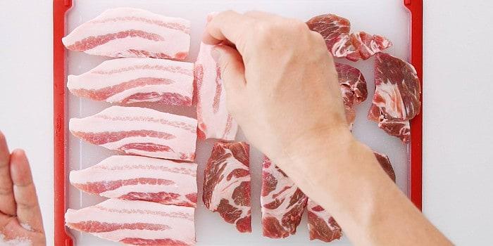 Salting pork belly and pork shoulder slices.