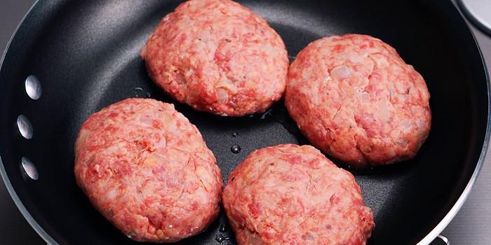 Raw hamburg steaks in a frying pan.