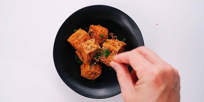 Garnishing crispy tofu bites with scallions.