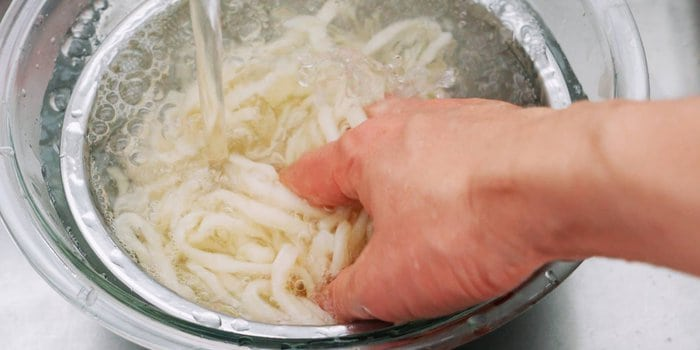 Washing udon noodles to remove extra starch.
