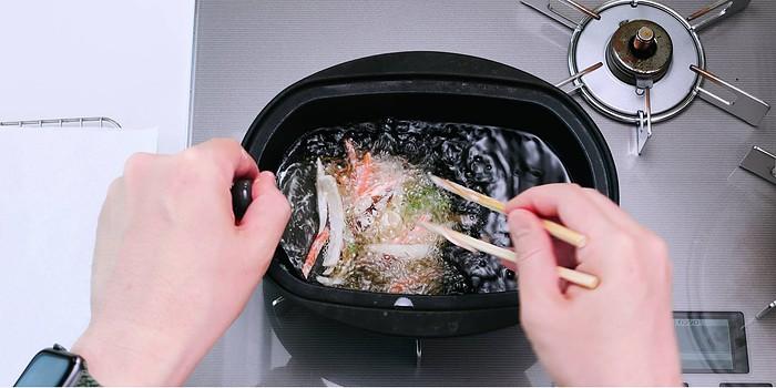 Adding kakiage tempura fritter to hot oil to deep-fry.