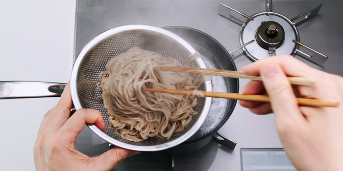 Transferring the cooked soba from the pot to a strainer.