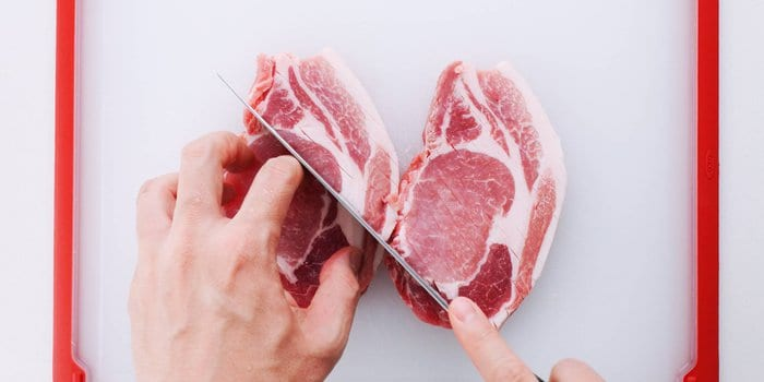 Cutting slits into pork chops for making tonkatsu