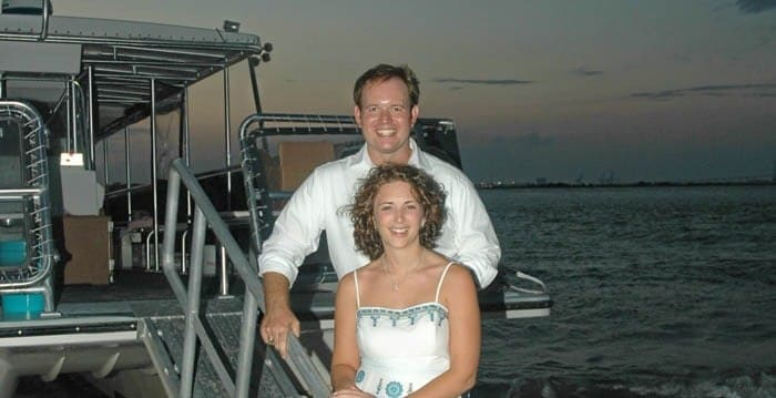 Bride and groom taking a picture on the Sandlapper Tours boat with the sunset in the background. Wedding dinner cruise Charleston SC