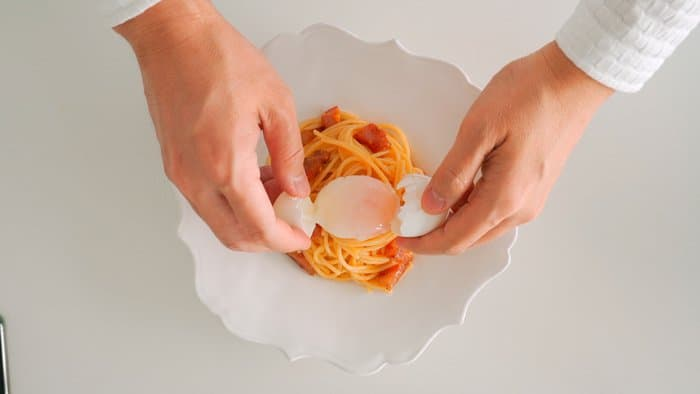 Topping Spaghetti Carbonara with a slow cooked egg.
