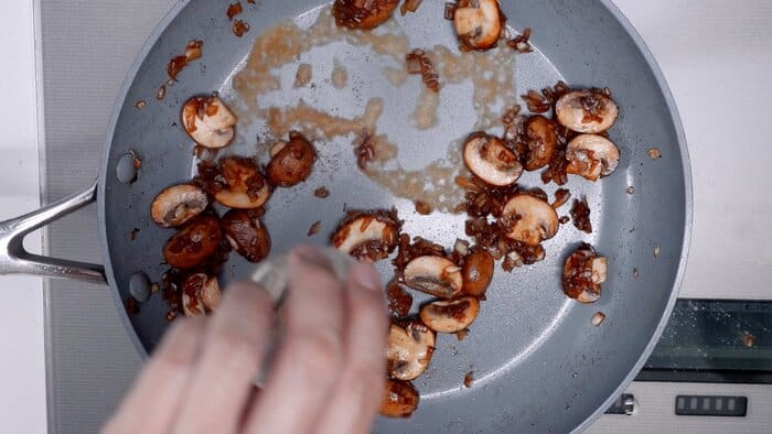 Deglazing the pan with sautéed mushrooms and onions with rum.