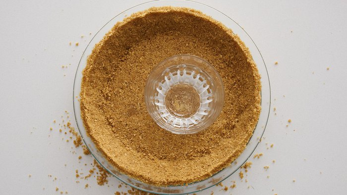 Pressing graham cracker crumbs into pie dish for key lime pie.