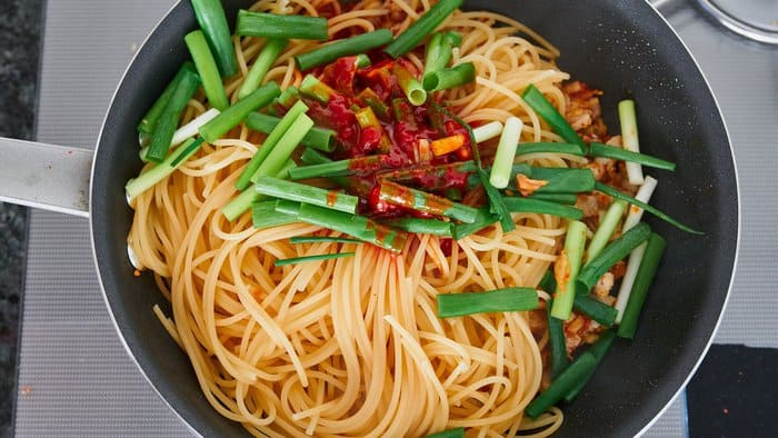 Finish the kimchi pasta by adding the scallions and sauce and tossing to coat evenly.