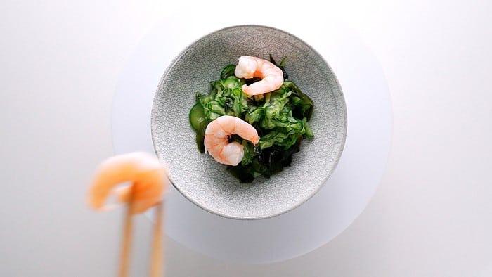 Placing shrimp on top of Sunomono (Japanese Cucumber Salad)