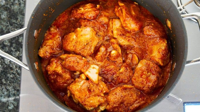 Add coconut milk and return the chicken to the rendang sauce.
