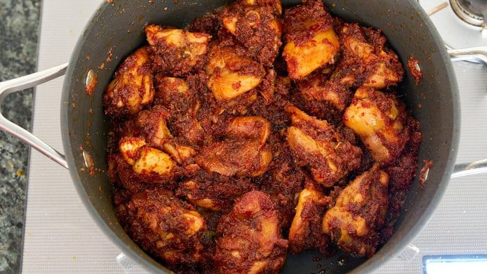 Add the kerisik to the chicken rendang and fry until there is no sauce left.