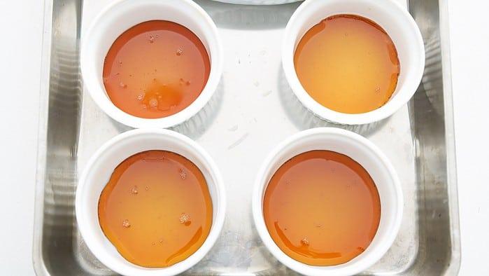 Caramel in the bottom of ramekins for making panna cotta.
