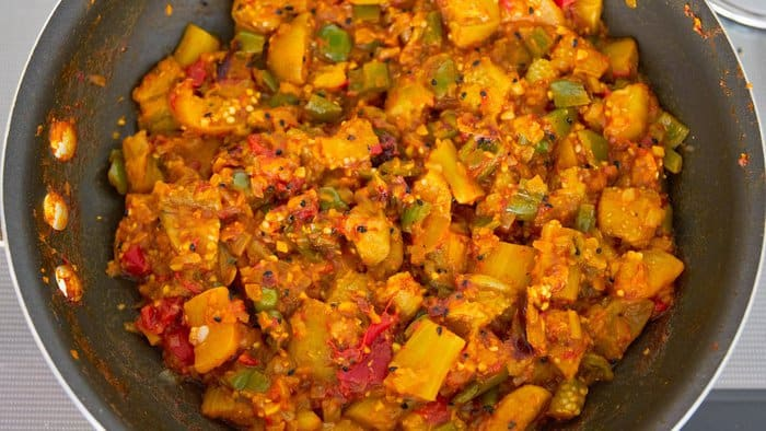 Finished eggplant curry is vibrant both in color and taste with tender eggplant pungent spices and tangy tomatoes.