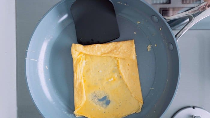 Layer of egg in a round frying pan being rolled up for Tamagoyaki.