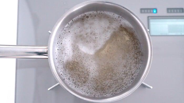 Konbu dashi boiling in a stainless steel pot.