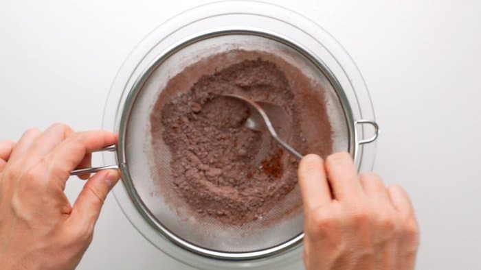 Sifting flour, cocoa powder, salt, and baking powder together for making brownies.
