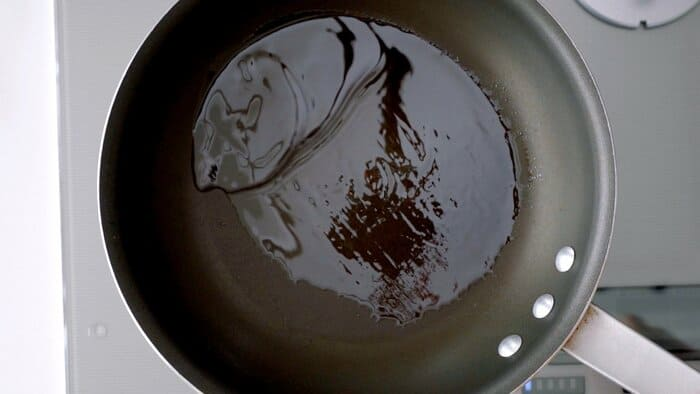 Hot oil in a non-stick frying pan.
