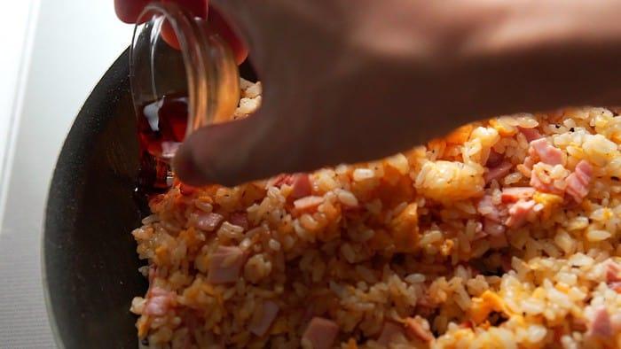 Seasoning yakimeshi with soy sauce.