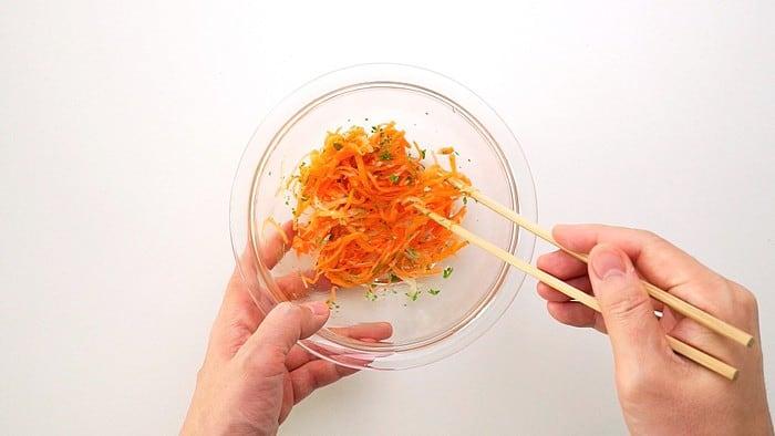 Mixing carrot salad with chopsticks.