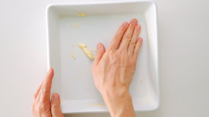 Buttering casserole dish for making Doria.