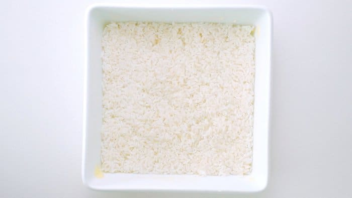 Layer of rice in buttered casserole dish.