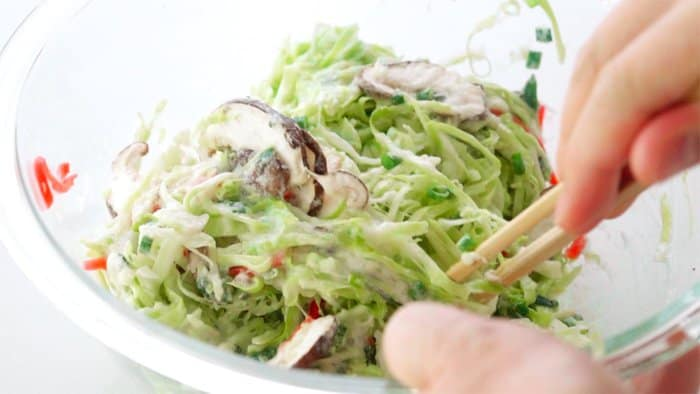 Mixing Okonomiyaki batter together in a glass bowl with chopsticks.