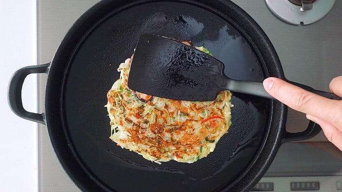 Pressing on Okonomiyaki with a spatula.