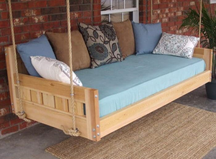 Rustic porch swing with ropes. Outdoor home decorating ideas.