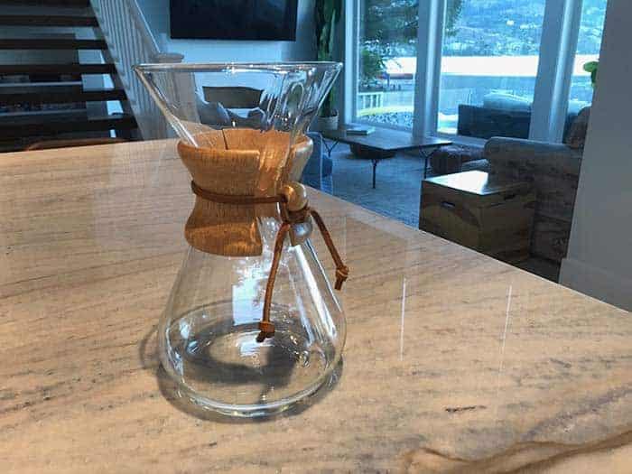 A shiny glass Chemex sitting on a kitchen counter