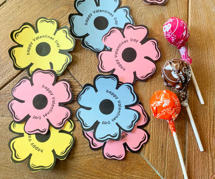 cut out flowers with lollipops laying beside them on a table