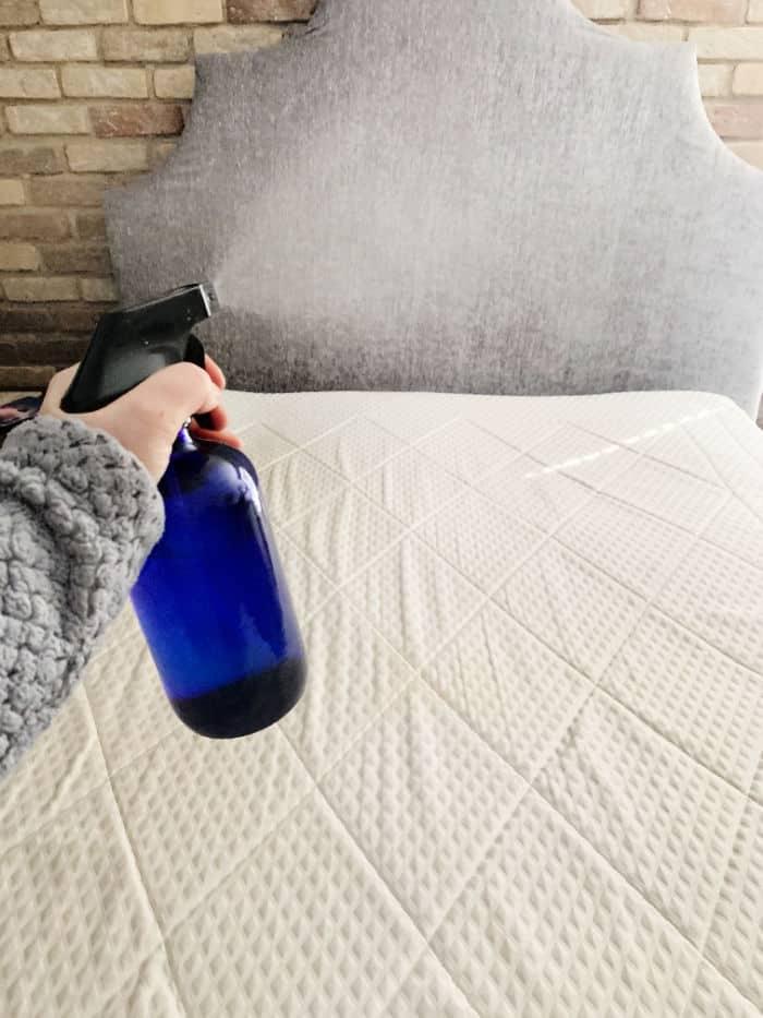 Spraying vinegar onto a mattress.
