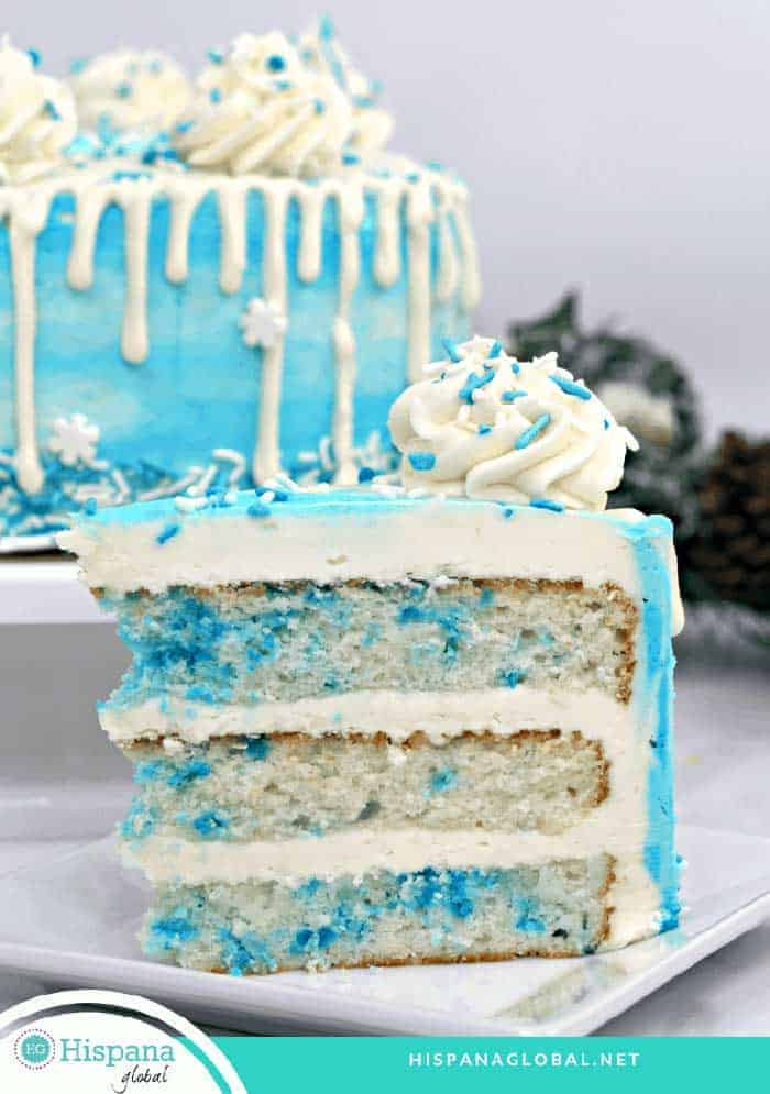 A slice of blue and white cake in front of a blue and white cake decorated for the movie Frozen