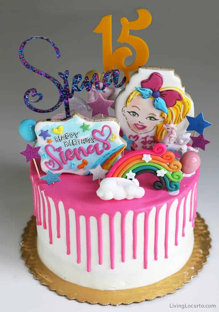 JoJo Siwa Birthday Cake. Hot Pink Drip Cake with colorful rainbow cookies and cake toppers.