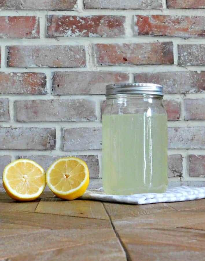 homemade bleach alternative in mason jar with sliced lemons beside it
