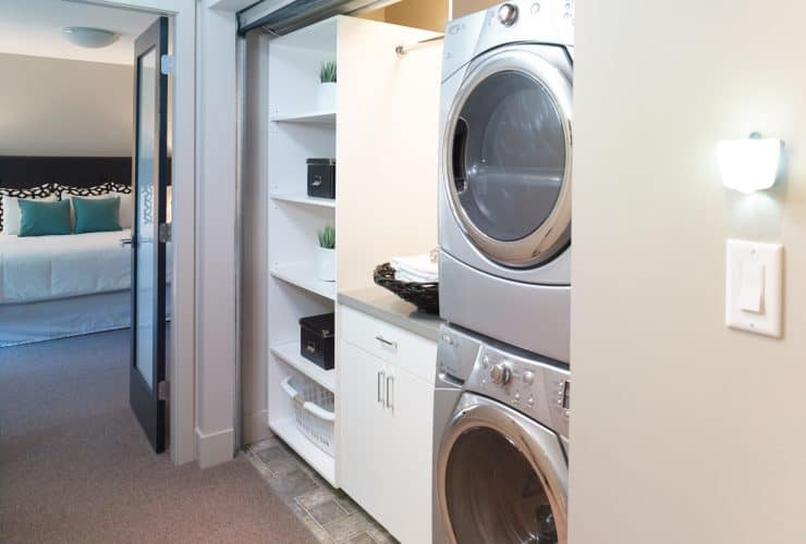 the laundry closet behind the roll up corrugated metal door is completed with cabinets and stacked washer and dryer
