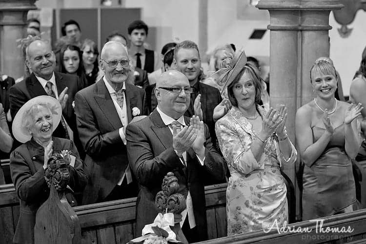 Guest clapping at wedding couple